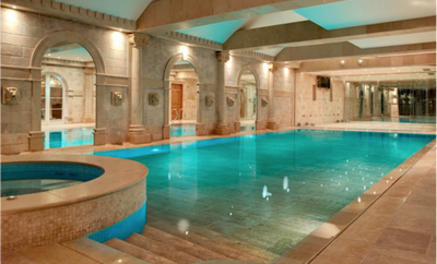 Indoor pool with light brown paving