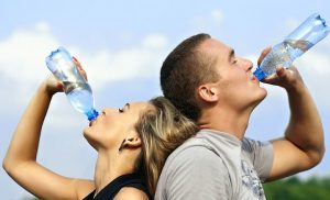 man and woman with backs to each other, drinking water