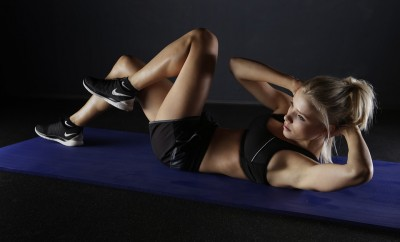 Woman on an exercise mat doing sit ups