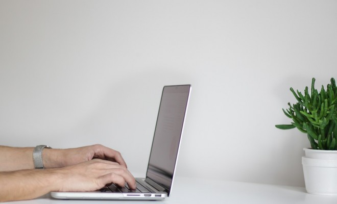 Laptop on a white table with masculine hands typing away