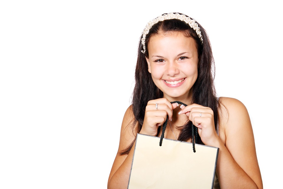 woman smiling holding a shopping paper bag