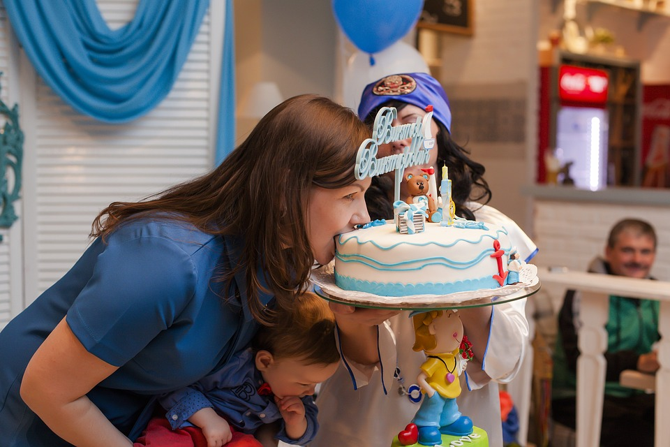 woman leaning over in blue top to speak to a child but cake covers her face