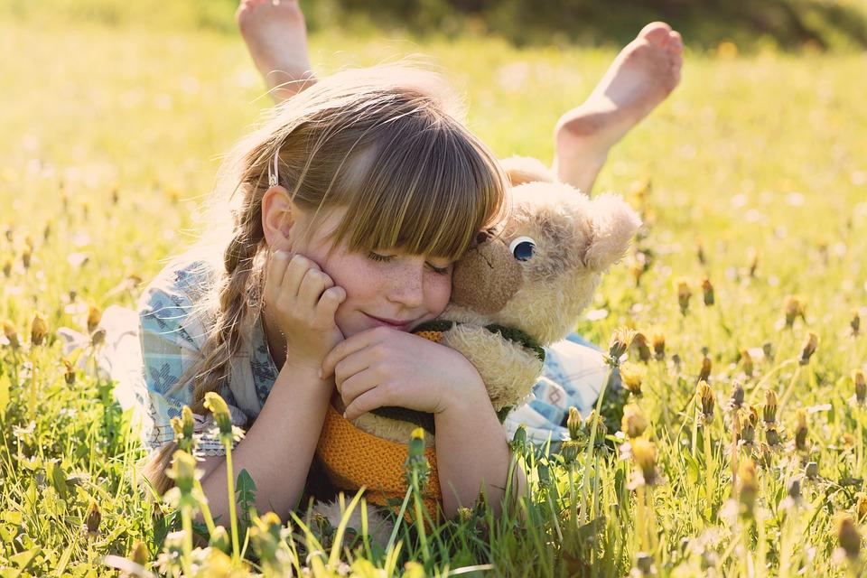 Little girl in a field of flowers, cuddling a teddy bear
