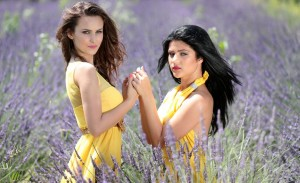 Two young women in a lavender field both wearing yellow dresses