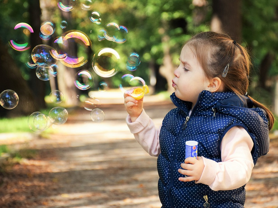toddler in blue vest blowing bubbles in a park