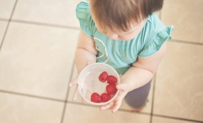 a toddler holding a white bowl with 5 strawberries in it
