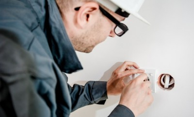 electrician fixing a power point on the wall