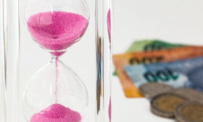 pink sand hour glass with money on background
