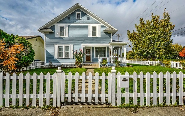 blue house enclosed with white picked fence