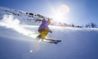 skier with yellow bottoms and blue jacket skiing down hill