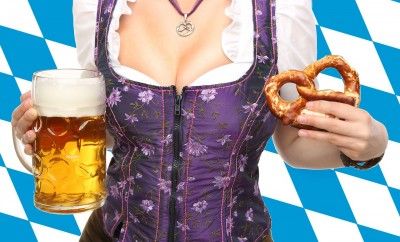 woman holding a glass of beer and a pretzel in each hand