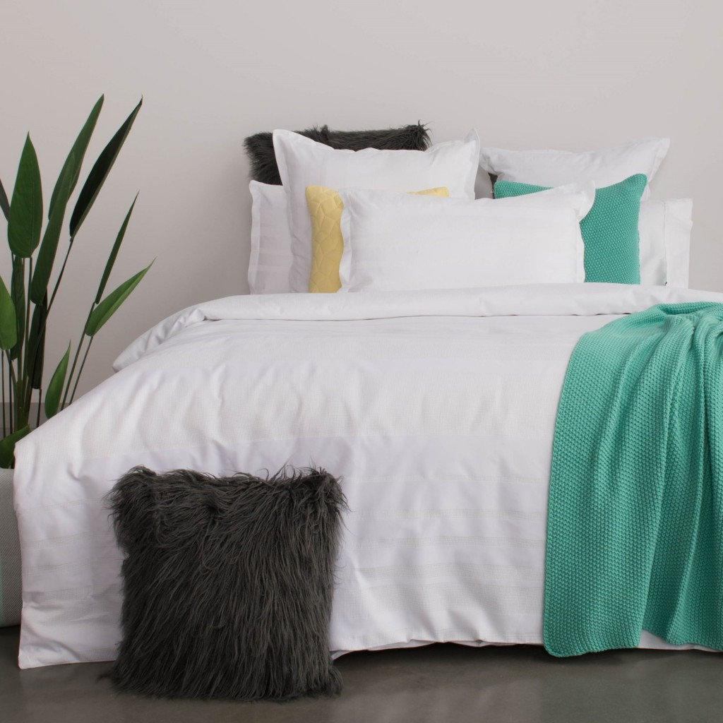 white bedding with a green throw and one yellow and green pillow