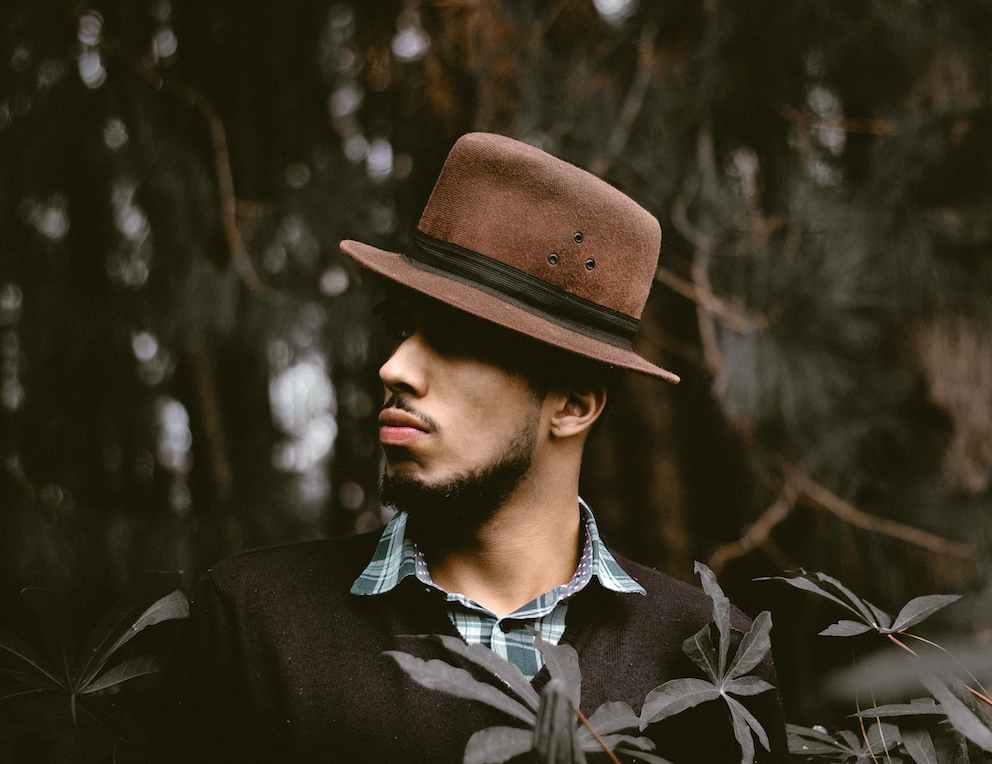 Young men wearing a fedora and a brown learther jacket in a black background