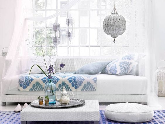 white couch with blue cushions and white walls