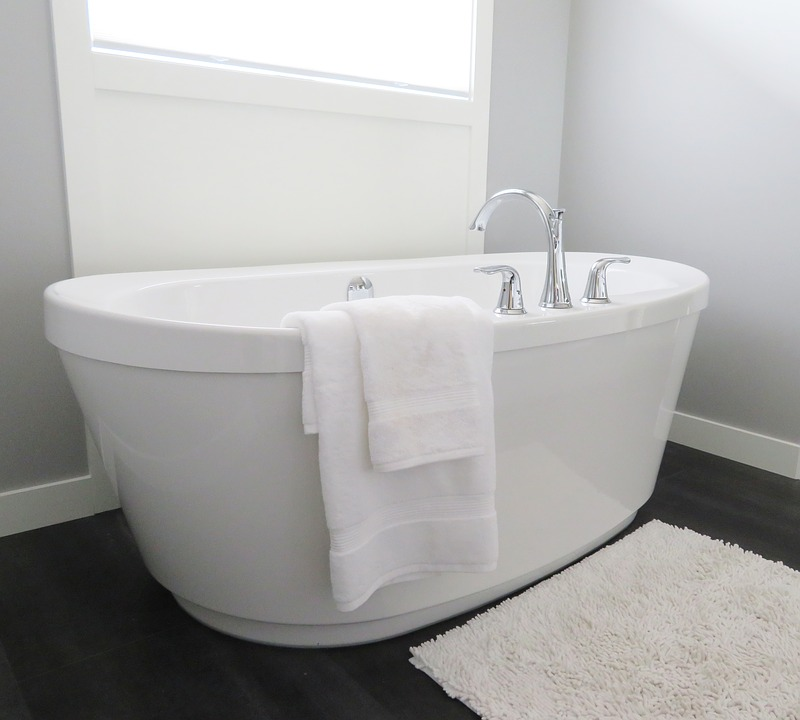 Bath tub with a white towel hanging by one side