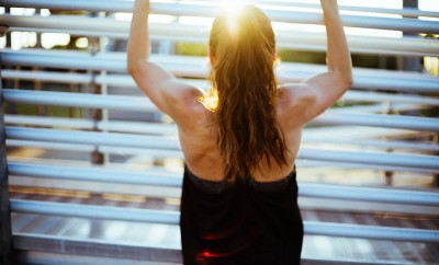 woman with back towards doing chin ups