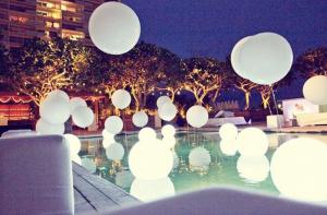 White balloons surrounding a pool at night
