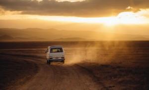 Car in the sandy horizon in golden hews