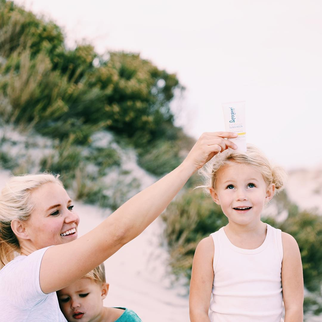 Blond mum at the beach with toddler in her lap and placing object on top of eldest child's head