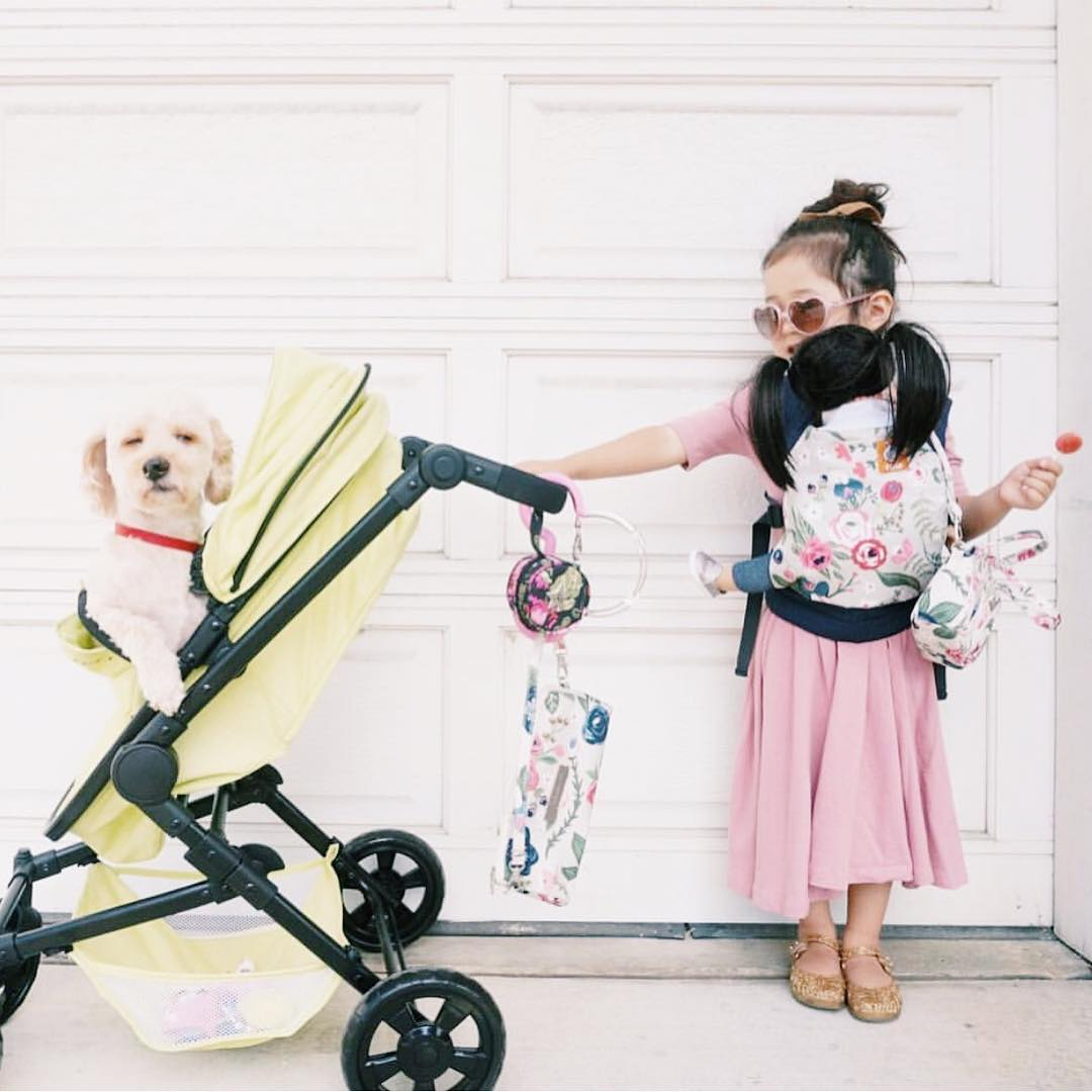 Little girl playing mum, with her dog in the pram and doll wrapped around her waist