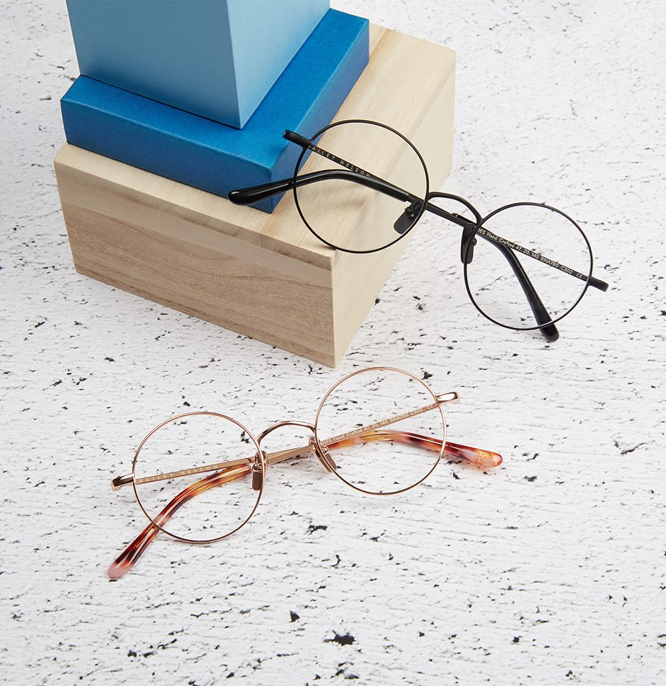 two pair of glasses leaning on wooden boxes