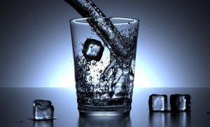 A glass of water in a deep blue background with ice cubes around ti