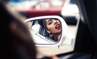 Woman driver looking into the car side mirror