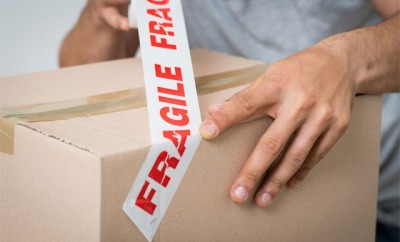 packing a moving box and tap with 'fragile'