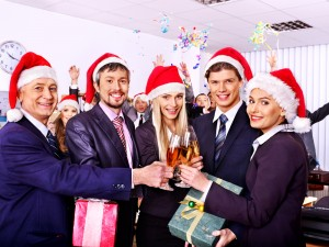 Co-workers wearing Christmas hats toasting a drink