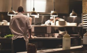 restaurant kitchen with back of a chef chopping food