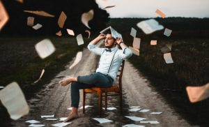 creative depiction of a man sitting on a chair in the middle of a dirt road while paper flies arund him