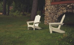 two outdoor white chairs in manicured lawn