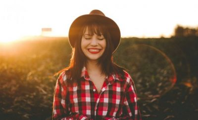 Woman wearing a hat and checker shirt smiling