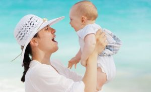 woman wearing a white hat and holding a baby up to her face