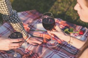 couple on a picnic enjoying a glass of red wine