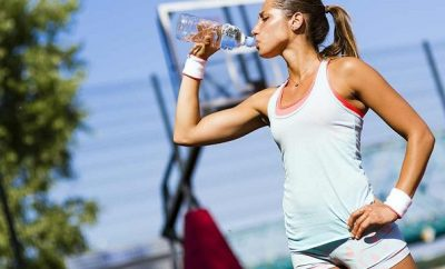 Woman in sports gear drinking mid exercise