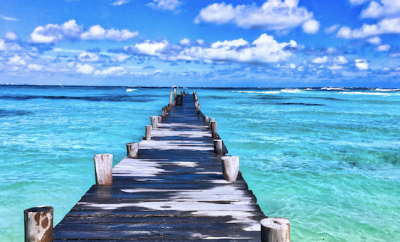 wooden walking bridge with blue ocean and sky