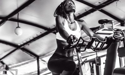 black and white woman in a gym bike exercising