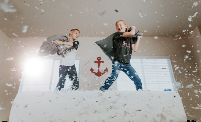 two boys on top of bed pillow fighting