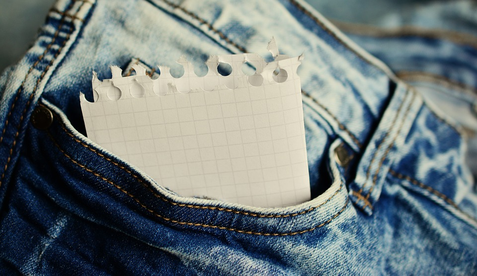 jeans pocket holding a folded piece of paper