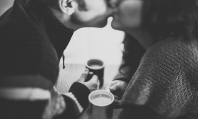 Couple holding cups of coffee and kissing