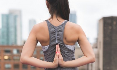 Woman holding a yoga pose facing city skyscrapers.