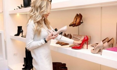 Blond lady in a white top shopping for red shoes
