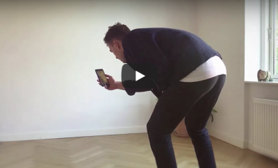 Man bending over in an empty room taking a photo with a mobile phone