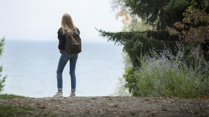 Young woman with backpack looking onto the ocean