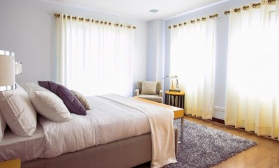 master bedroom with a arm chair between two windows with white drapes