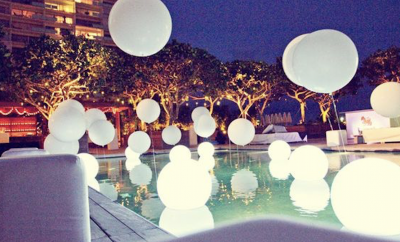 White balloons surrounding a pool at night
