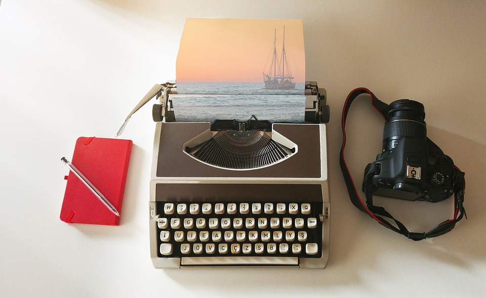 typewriter with a red notebook on the left handside