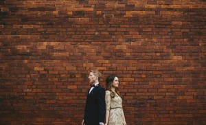 Couple back to back against a red brick wall for a wedding picture