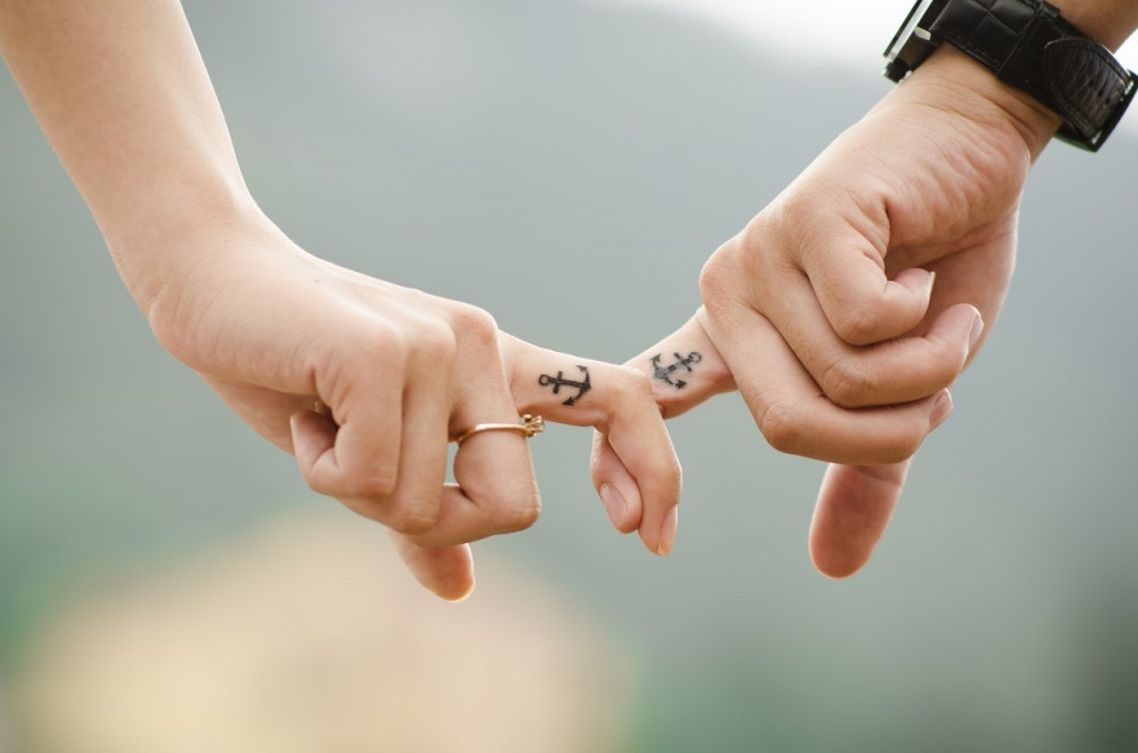 ouple holding hands by index tattoo fingers with a anchor